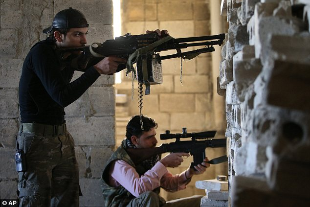 Fighting back: Free Syrian Army fighters take their positions as they observe official Syrian army forces base of Wadi al-Deif, at the front line of Maaret al-Numan town, in the Idlib province