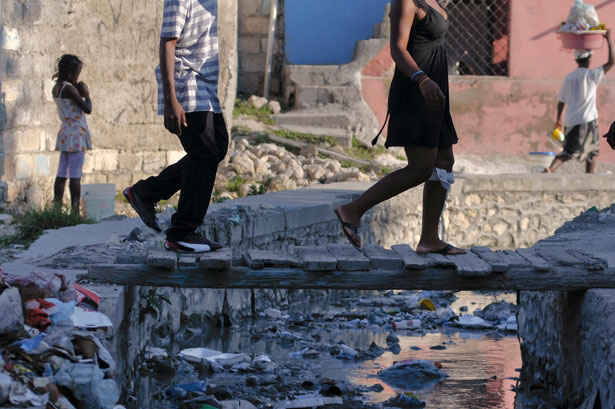 People walk across a tiny overpass as raw sewage flows beneath in an open sewage in Port-au-Prince September 4, 2012. REUTERS/Swoan Parker