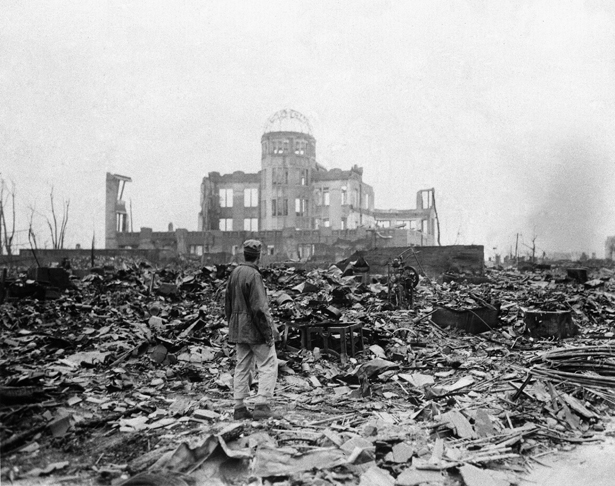 An allied correspondent stands in a sea of rubble before the shell of a building in Hiroshima September 8, 1945, a month after the first atomic bomb ever used in warfare was dropped by the US. (AP Photo/Stanley Troutman)