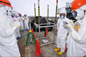 Reporters inspect an observation well which is dug to take underground water samples near Fukushima Dai-ichi nuclear plant Unit 1 of Tokyo Electric Power Co., in Okuma, Fukushima prefecture, northeastern Japan. Kyodo News/AP/File