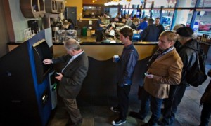 Customers line-up to use the world's first ever permanent bitcoin ATM at a coffee shop in Vancouver, British Columbia. Photograph: Andy Clark/Reuters