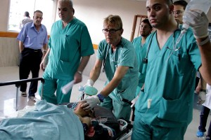 Dr Mads Frederick Gilbert (centre) at Al-Shifa hospital on July 17 2014, treating a wounded Palestinian child, after an Israeli air strike killed 4 children and wounded 5 others.