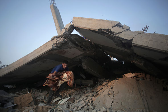 Palestinians salvage what they can of their belongings from the rubble of a house destroyed by an Israeli airstrike in Gaza City. AP/Khalil Hamra