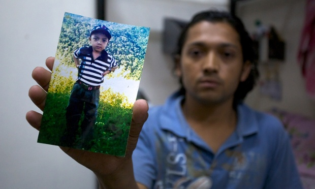 Ujjwal Bishwakarma holds a photo of his son, Ashish. Pete Pattisson for the Guardian