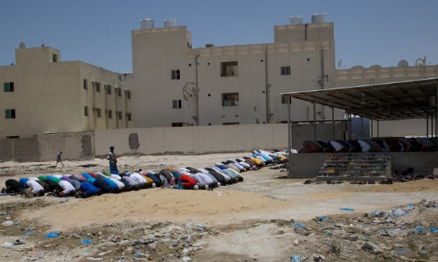Migrant workers attend prayers at a makeshift mosque in a vast labour camp in Qatar. Photograph: Pete Pattisson for the Guardian