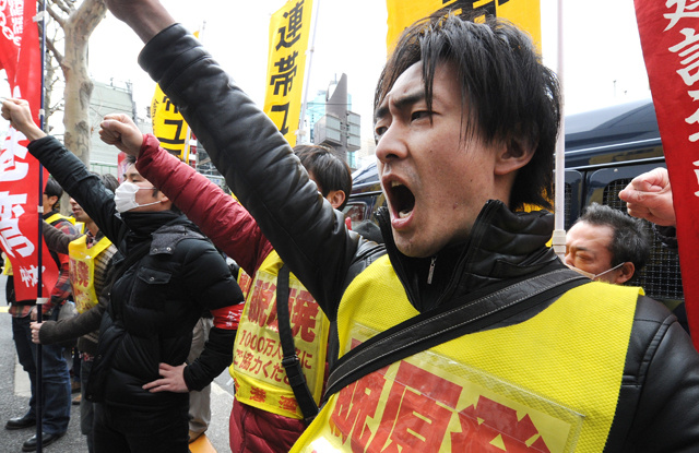 Fukushima nuclear workers and their supporters raise their fists in front of TEPCO headquarters during a rally in Tokyo on March 14, 2014. Toru Yamanaka/AFP/Getty Images