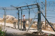A settler security officer locking a gate in a fence separating Palestinians from their land | UN