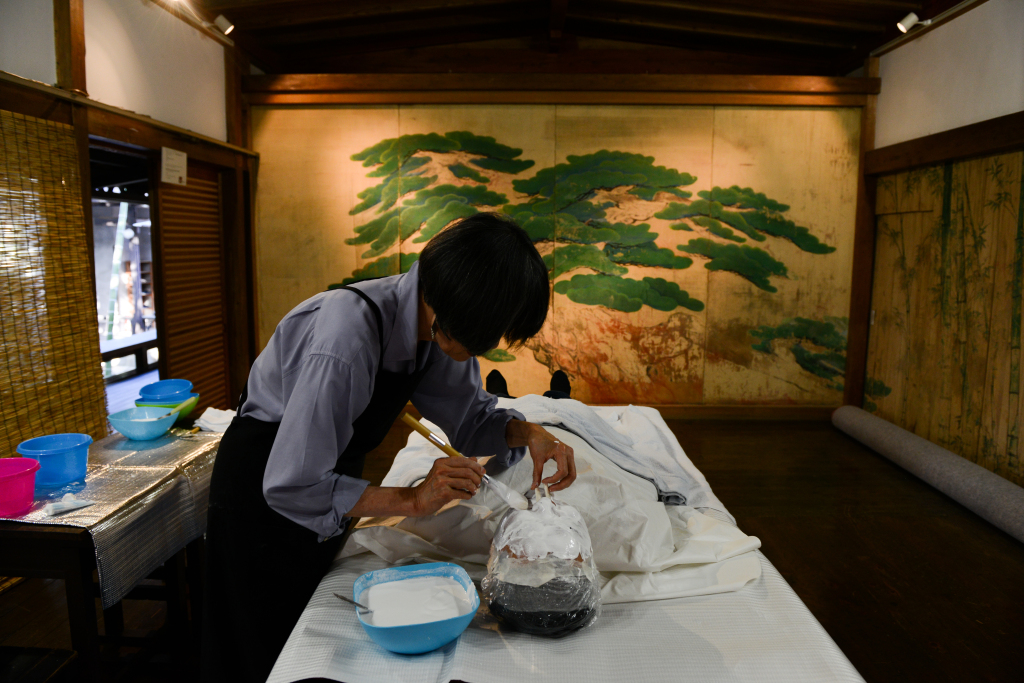 Kim Myong-hee, a Korean artist who has been living in Kyoto for almost four decades, puts plaster on Ryoma Yamanao, a young Japanese businessman, during a workshop for the Peace Mask East Asia project. (Noriko Hayashi/for The Washington Post)