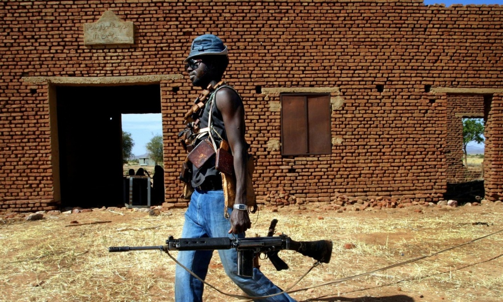A Sudan Liberation Army rebel passes an abandoned building in the desert west of El Fasher, the capital of North Darfur state, in 2004. Photograph: Finbarr O'Reilly/RTRPIX