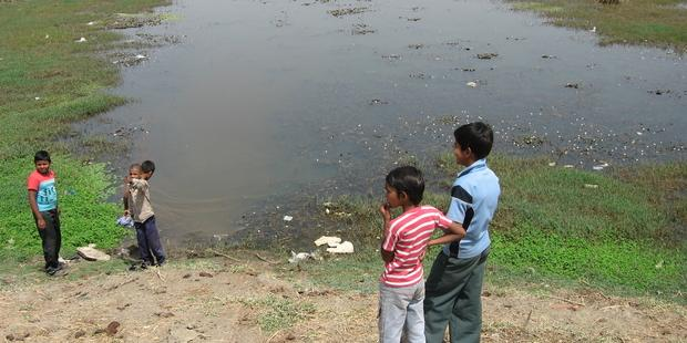 Children playing around the contaminated Solar Evaporation Pond in Bhopal, India.