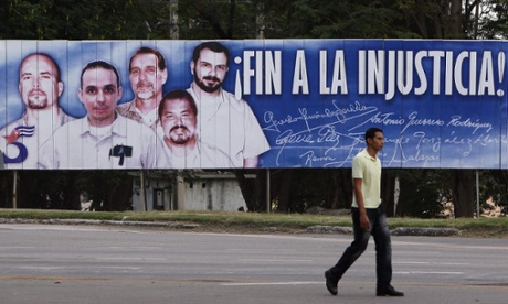 A man walks in front of a banner of the Cuban Five which says 'End the injustice'. Photograph: Alejandro Ernesto/EPA