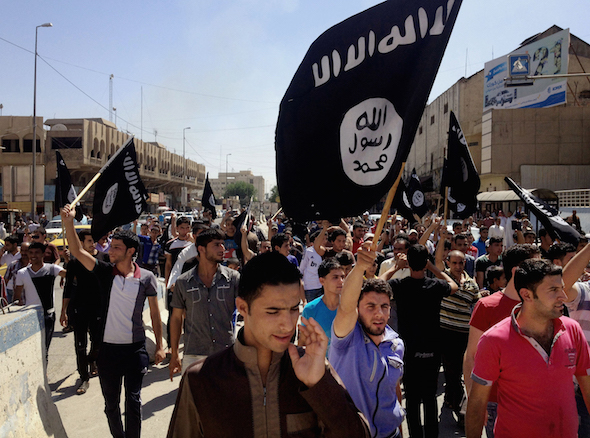Demonstrators chant Islamic State slogans last June as they carry the group's flag in front of the provincial government headquarters in Mosul in Iraq. AP photo