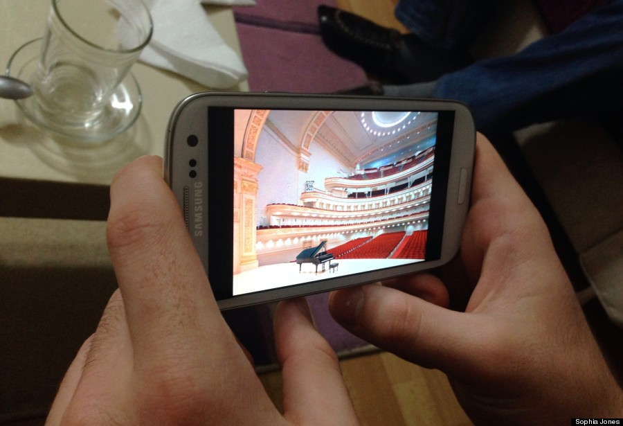 Tambi Asaad Cimuk excitedly pulls up a photo on his phone on Dec. 16 of Carnegie Hall, where he will be playing piano in January as part of a youth music competition.