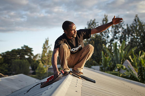 An employee with M-POWER installs a solar panel on a roof near the city of Arusha, in northern Tanzania. Courtesy of Mathieu Young/Off-Grid Electric