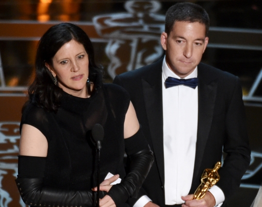 Laura Poitras and Glenn Grenwald accept the Oscar award. John Shearer/Invision/AP