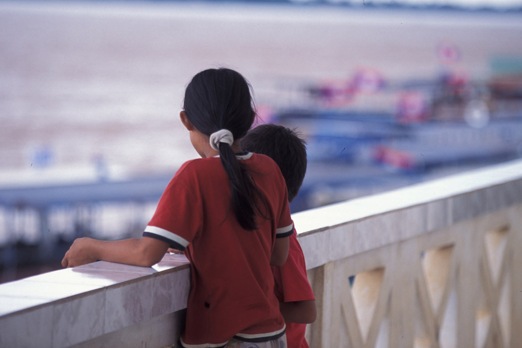 Two children stand on the balcony of an immigration office in Laos. The UN Children's Fund (UNICEF) works with the Government and partners to stem the flow of young people into dangerous labour agreements outside the country. Photo: UNICEF/LaoPDR04713/Jim Holmes