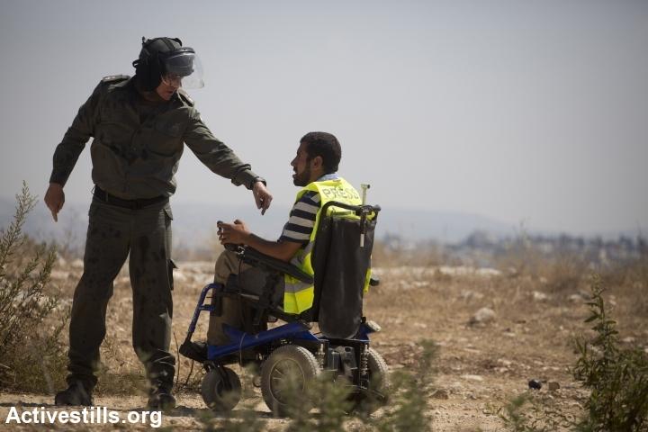 An Israeli soldier speaks to a wheelchair-bound Palestinian protester during a demonstration in Bil'in. (photo: Oren Ziv/Activestills.org)