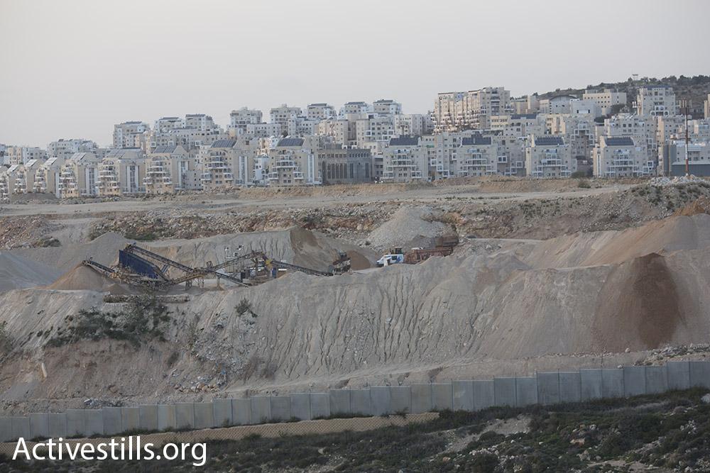 Beyond the separation wall, bulldozers expand the Modi'in Illit settlement bloc. (photo: Oren Ziv/Activestills.org)