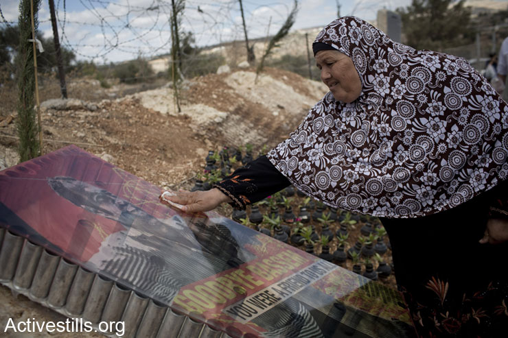 Palestinian Subhiya Abu Rahme cleans the memorial monument of her son, Bassem who was shot to death by an Israeli soldier during a protest in the village in 2009; October 4, 2013. The garden was set with many flowers put in empty gas canisters and inaugurated during the eight Bil'in popular struggle conference.