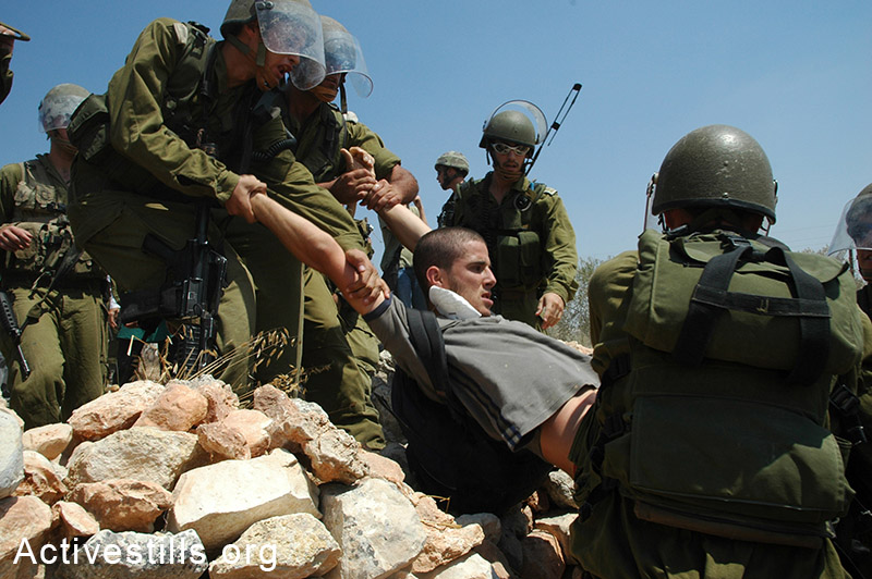 Israeli activist Ben Ronen is arrested by the army during the weekly protest against the building of the Wall in the West Bank village of Bil'in, August 26, 2005. (photo: Yotam Ronen / Activestills.org)