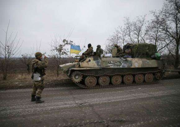 A convoy of Ukrainian armed forces including armoured personnel carriers, military vehicles and cannons prepare to move as they pull back from the Debaltseve region, in Paraskoviyvka, eastern Ukraine, February 26, 2015. Credit: Reuters/Gleb Garanich