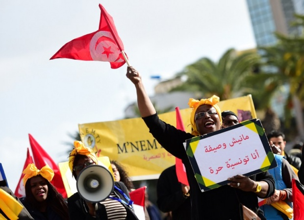 Photo: A woman holds a placard shouting slogans during a march at the end of the 2015 World Social Forum (WSF) in Tunis on March 28, 2015. AFP