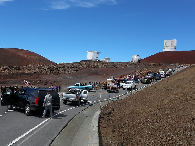 On October 7, 2014, protestors blocking the road, halted a groundbreaking ceremony for the Thirty Meter Telescope. (AP Photo/Hawaii Tribune-Herald, Hollyn Johnson)