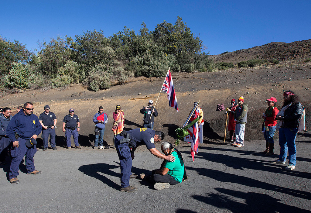 Protesters have for the past three weeks created a human blockade. More than 30 people have been arrested. On April 2, 2015, a Department of Land and Natural Resources Officer speaks with one of the activists. (AP Photo/Hawaii Tribune-Herald, Hollyn Johnson)