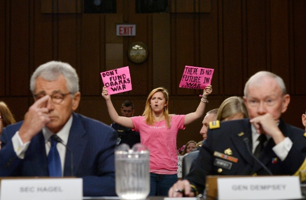 Anti-war activists protest as U.S. Defense Secretary Chuck Hagel (L) and Chairman of the Joint Chiefs of Staff General Martin Dempsey (R) testify before the Senate Armed Services Committee on Capitol Hill in Washington, D.C., the United States, Sept. 16, 2014 [Xinhua]