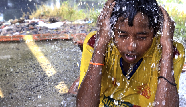 A young boy in Kolkata, India keeps himself cool amid a relentless heat wave that has killed thousands of people in his country. Photo Credit: Saikat Paul / Shutterstock.com