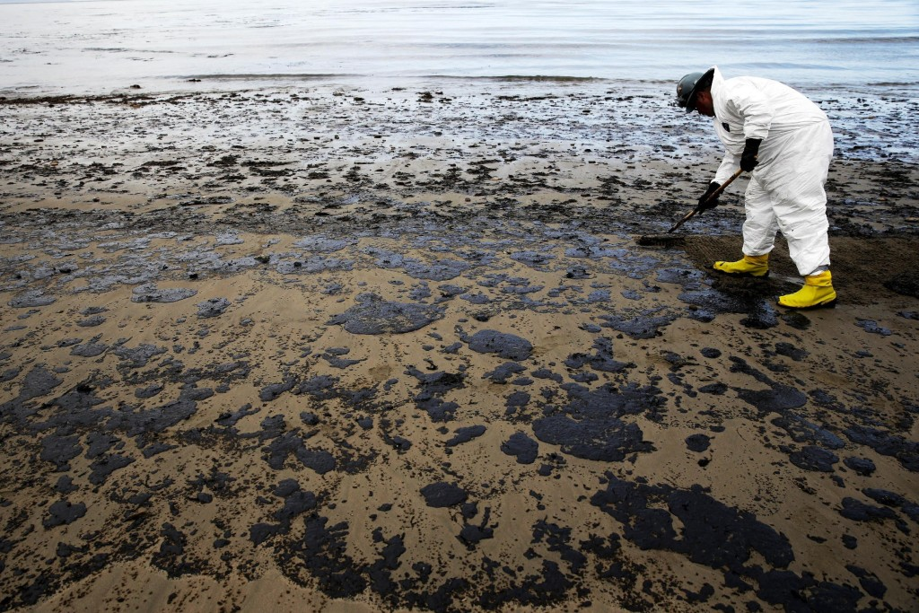 "FILE - In this May 21, 2015, file photo, a worker removes oil from sand at Refugio State Beach, north of Goleta, Calif. An underground pipe, owned by Plains All American Pipeline, spewed oil down a culvert and into the Pacific on May 19 before it was shut off. Democratic U.S. Sens. Barbara Boxer and Dianne Feinstein say the response to the oil spill that blackened beaches and created a 10-square-mile slick on the ocean was ""insufficient."" and called on federal regulators to provide more details on the activities and decisions by Plains. (AP Photo/Jae C. Hong, File)"
