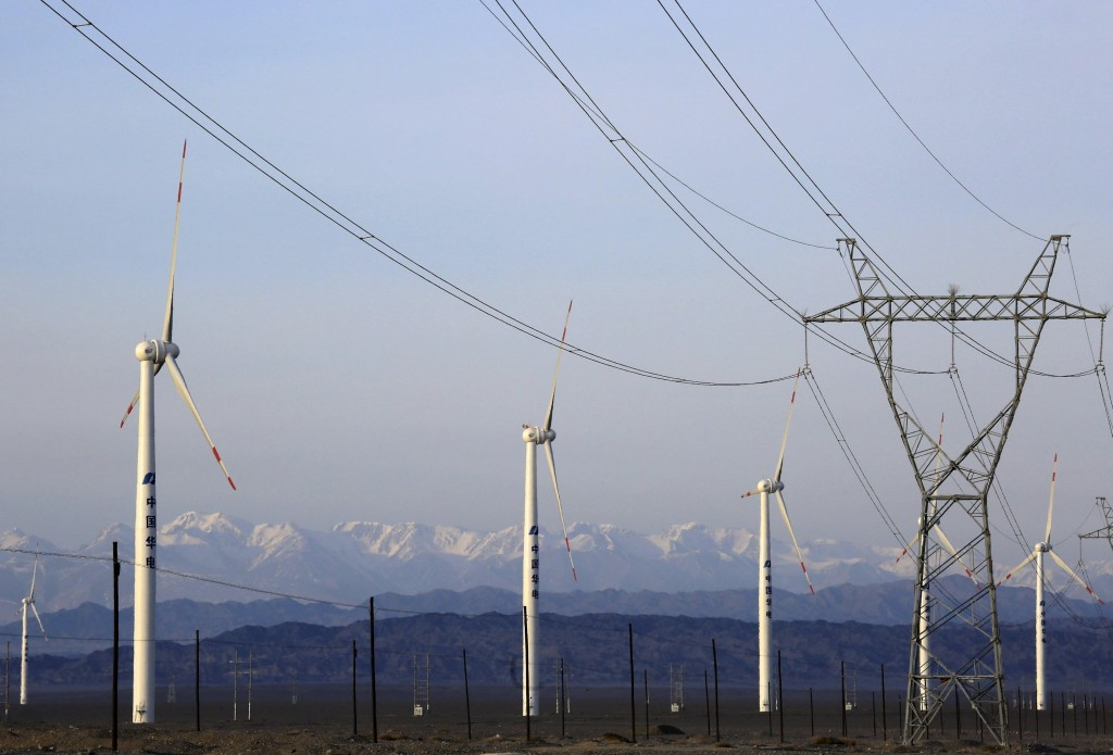 An electricity pylon is seen next to wind turbines at a wind power plant in Hami, Xinjiang Uighur Autonomous Region, China, March 21, 2015. China's wind farm firms are feeling the heat as state grid operators deliberately delay hooking them up and cut back on purchases, wasting about a fifth of the total wind power output or enough electricity to run Beijing for 40 days. Picture taken March 21, 2015. REUTERS/Stringer