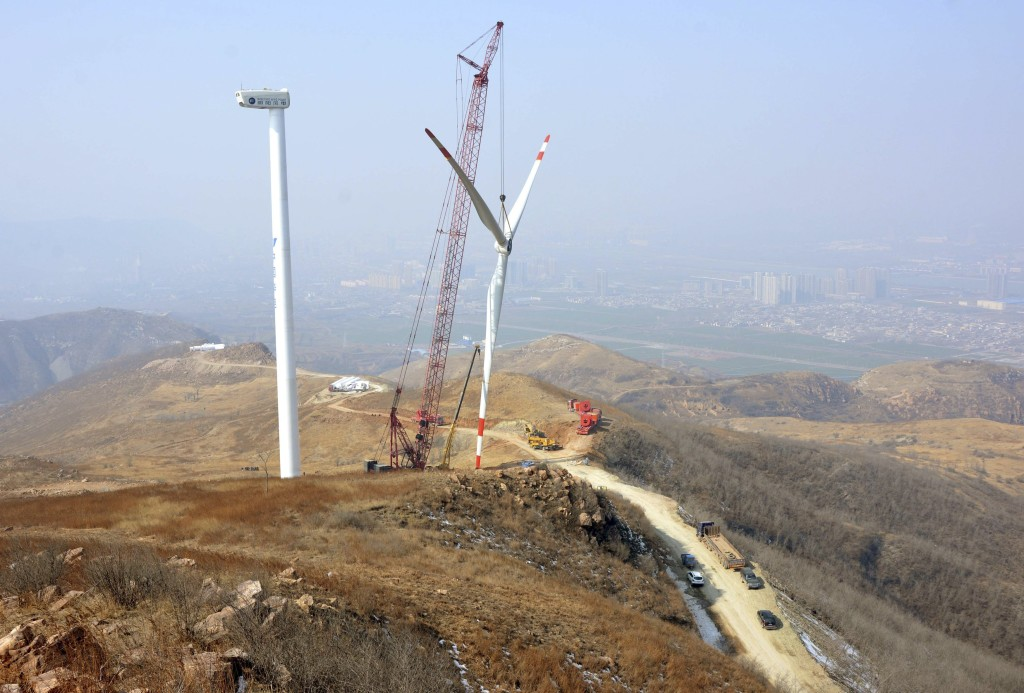 The rotor blades of a wind turbine is lifted by a crane at a construction site of a wind power plant in Yiyang, Henan province, China, February 10, 2015. China's wind farm firms are feeling the heat as state grid operators deliberately delay hooking them up and cut back on purchases, wasting about a fifth of the total wind power output or enough electricity to run Beijing for 40 days. Picture taken February 10, 2015. REUTERS/Stringer