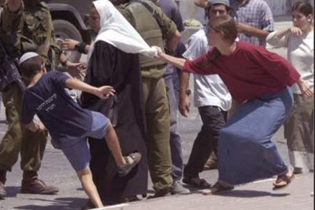 Jewish settlers attacking Palestinian lady. Palestine. Photo from Middle East Monitor.