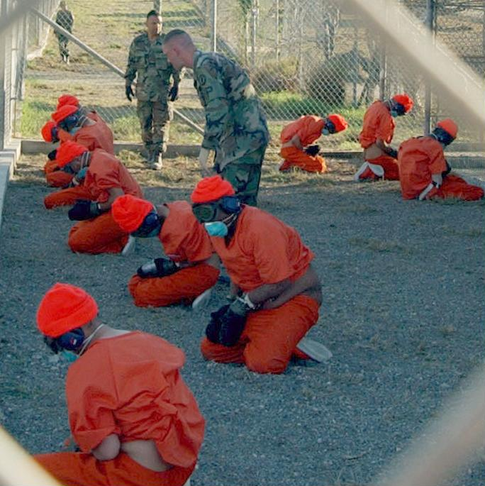Successful interrogation requires craft and empathy, not brute force. Pictured: Inmates kneeling on rocks. Guantanamo Bay Detention Camp. (Photo: Shane McCoy / Wikipedia)