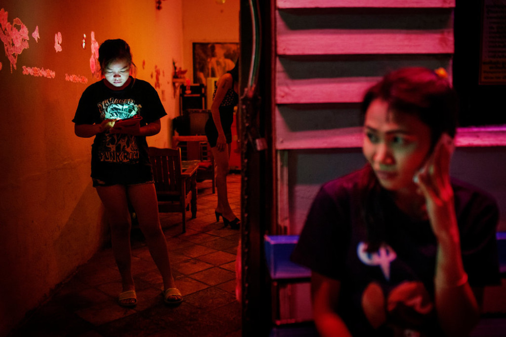 Prostitutes waited for customers outside a karaoke bar and brothel in Songkhla, Thailand. Credit Adam Dean for The New York Times