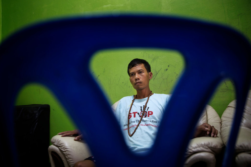 Lang Long, 30, watched television in a safe house in Songkhla. Mr. Long, a Cambodian, was rescued from a fishing boat where he was forced to work on for three years and was often restrained with shackles. Credit Adam Dean for The New York Times