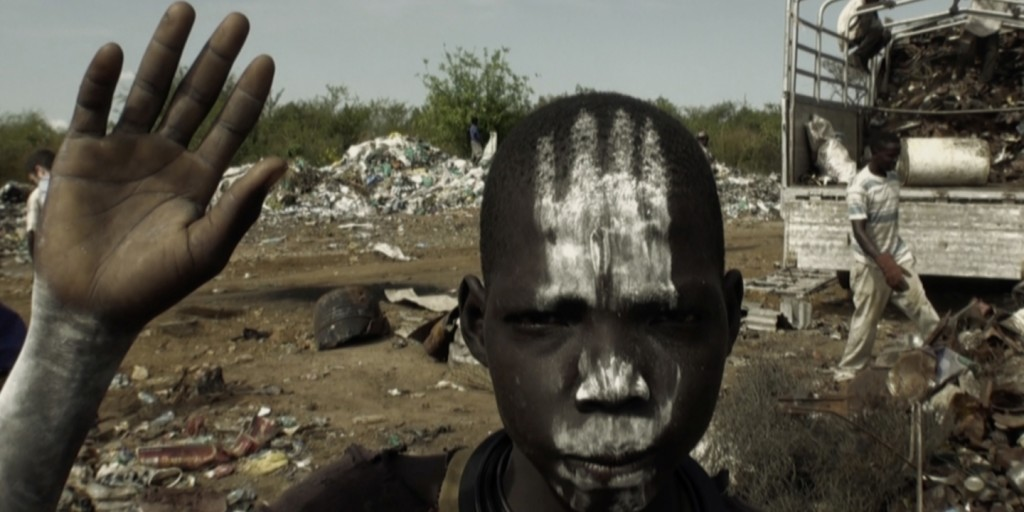 Adolescent boy from the Bari tribe, South Sudan, apparently imitating the tribal traditions of warriors putting ashes on their body. This ash is produced from burning trash.