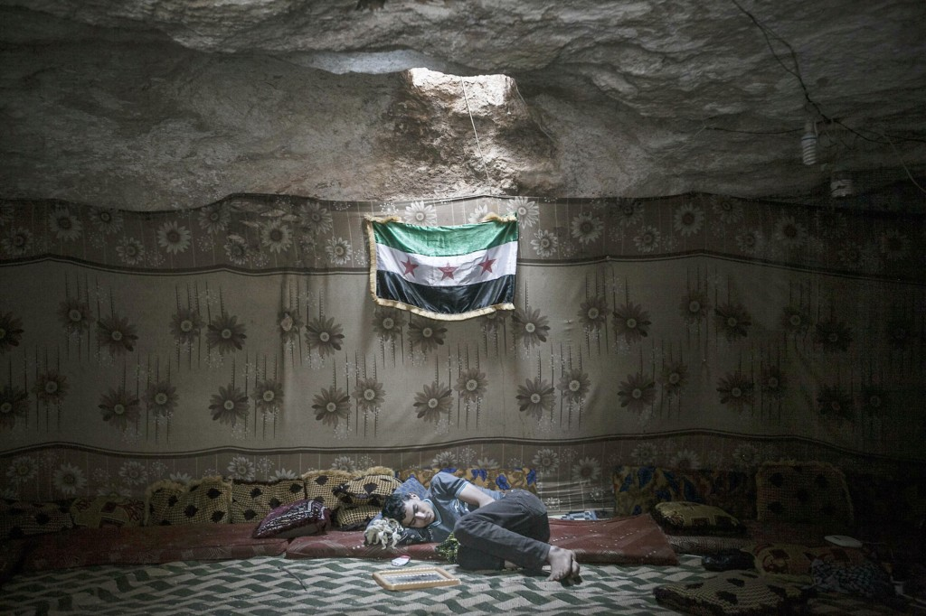 A Free Syrian Army fighter rests inside a cave at a rebel camp in Idlib, Syria on 17th September 2013. As of April 2015, moderate FSA rebels in Idlib have been supplanted by a US-backed rebel coalition led by Jabhut al-Nusra, al-Qaeda in Syria