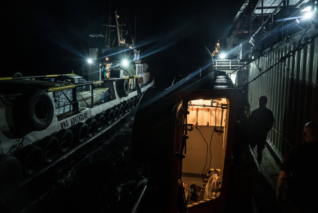 A smaller transport ship disconnected from the Resolution in the dead of night. CreditBen C. Solomon/The New York Times
