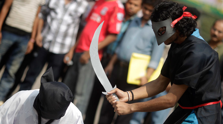 Members of Magic Movement, a group of young Bangladeshis, stage a mock execution scene in protest of Saudi Arabia beheading of eight Bangladeshi workers in front of National Museum in Dhaka October 15, 2011. © Andrew Biraj / Reuters
