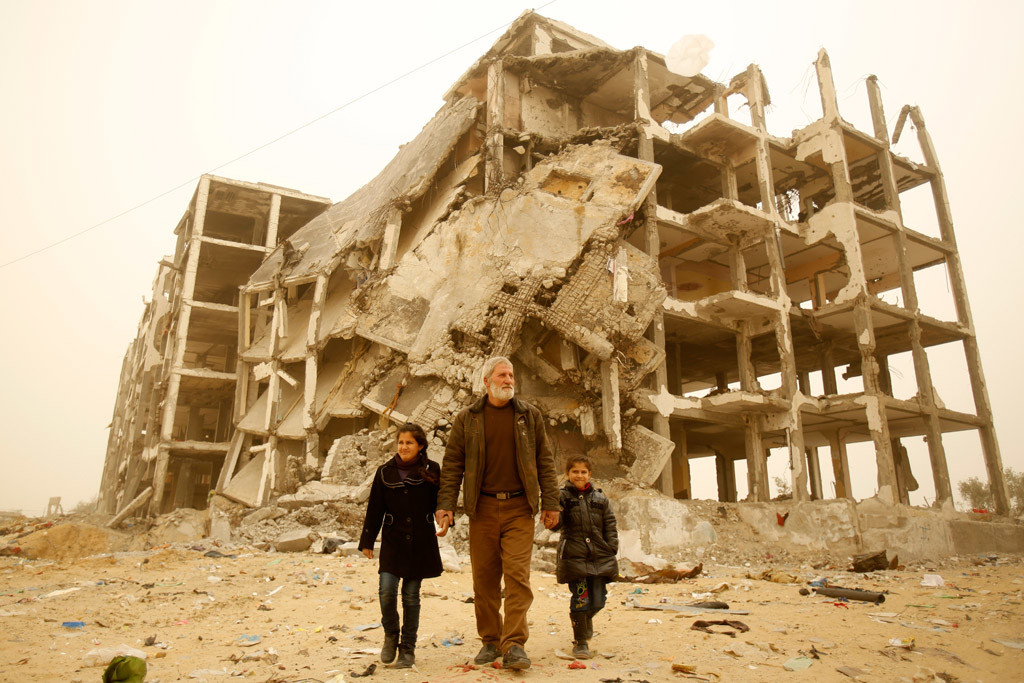 A man holds the hands of his granddaughters near the remnants of the residential towers where the girls used to live, in the city of Beit Lahia, in the northern Gaza Strip. Photo: UNICEF/Eyad El Baba