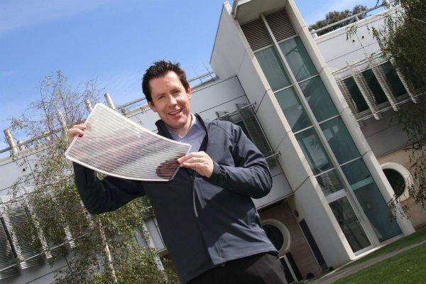 Photo: CSIRO materials scientist Dr Scott Watkins holds a sheet of flexible solar cells. (Supplied: CSIRO)
