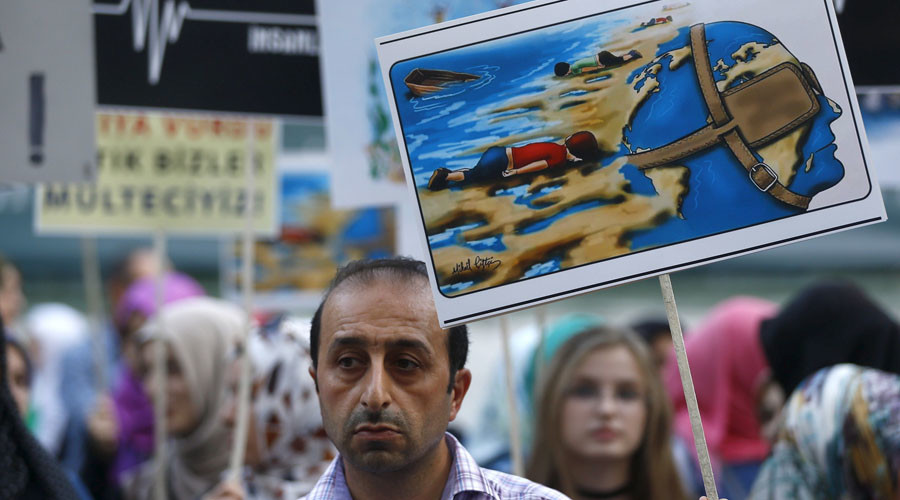 A man holds a poster with a drawing depicting drowned Syrian toddlers during a demonstration for refugee rights in Istanbul, Turkey, September 3, 2015.