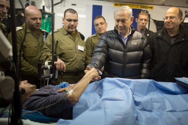 """Israeli Prime Minister Benjamin Netanyahu and Defence Minister Moshe Ya'alon next to a wounded mercenary, Israeli military field hospital at the occupied Golan Heights' border with Syria, 18 February 2014″"
