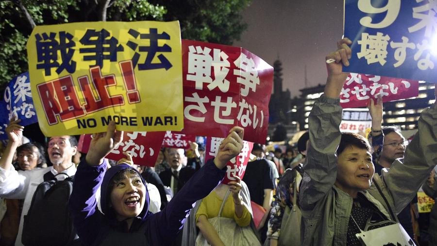 Demonstrators shout slogans and hold banners reading 'No War!' outside Japan's parliament in Tokyo. (Franck Robichon / European Pressphoto Agency)