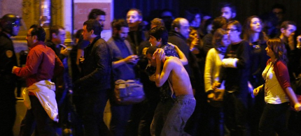 Wounded people flee a hostage situation at the Bataclan theater in Paris, November 13, 2015. (photo: Yoan Valat/EFA/Landov)