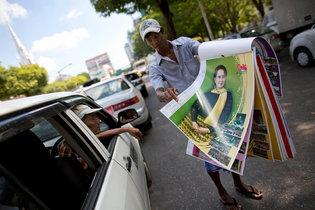 A street vendor in Yangon, Myanmar, displays a 2016 calendar featuring Daw Aung San Suu Kyi. Credit Gemunu Amarasinghe/Associated Press