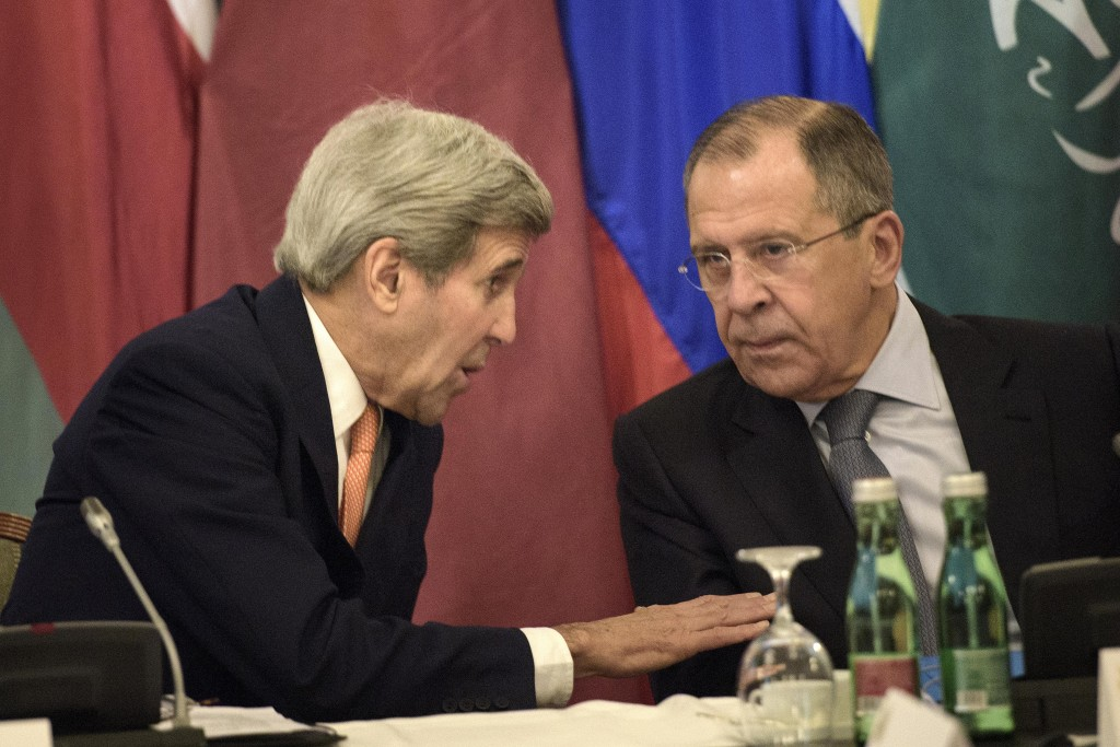 US Secretary of State John Kerry, left, and Russian Foreign Minister Sergey Lavrov share a word prior to the start of the Syria talks at a hotel in Vienna, Austria, Friday, Oct. 30, 2015. CREDIT: Brendan Smialowski/Pool Photo via AP