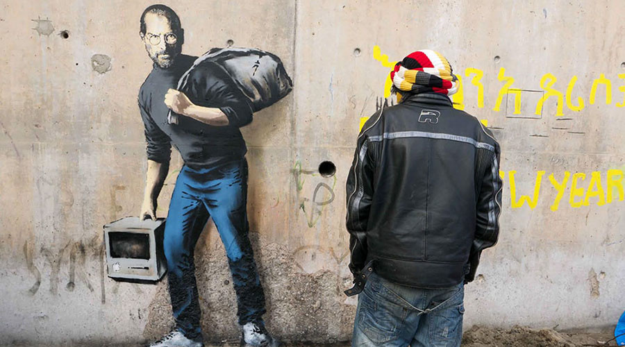 """The picture of the late pioneer of the microcomputer revolution, Steve Jobs, carrying a rucksack appears on the wall in infamous Jungle refugee camp in the French port of Calais. """"The son of a migrant from Syria,"""" the description under the picture reads. © banksy.co.uk"""